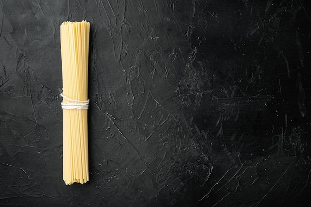 全粒粉スパゲッティ、黄色の長い未調理の乾燥パスタセット、黒い石のテーブル、上面図フラットレイ、コピースペース付き