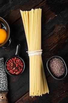 全粒粉スパゲッティ、黄色の長い未調理の乾燥パスタセット、古い暗い木製のテーブル、上面図フラットレイ