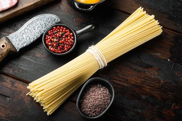 全粒粉スパゲッティ、黄色の長い未調理の乾燥パスタセット、古い暗い木製のテーブル