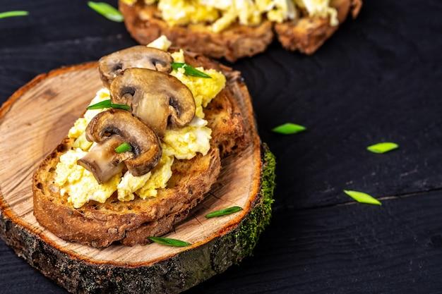 버섯과 코티지 치즈를 곁들인 스크램블 에그를 곁들인 통밀 토스트. 건강한 아침 식사 또는 브런치. 레스토랑 메뉴, 다이어트, 요리 책 레시피.
