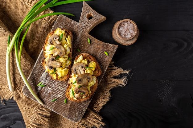 キノコとカッテージチーズのスクランブルエッグを添えた全粒粉トースト。健康的な朝食またはブランチ。レストランメニュー、ダイエット、料理本のレシピ。