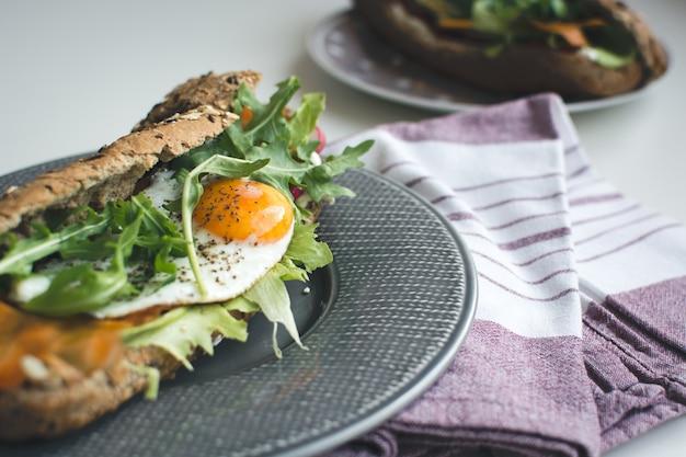 揚げた卵とアルーゴラを持つwholewheatバゲット