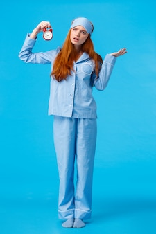 Why didnt you set alarm. confused and unsure upset attractive redhead woman in pyjama and sleep mask, shrugging perplexed staring questioned, holding clock, blue wall