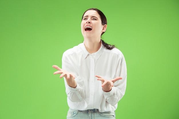 何故ですか。トレンディな緑のスタジオの背景に分離された美しい女性のハーフレングスの肖像画。若い感情的な驚き、欲求不満、当惑した女性。人間の感情、顔の表情の概念。