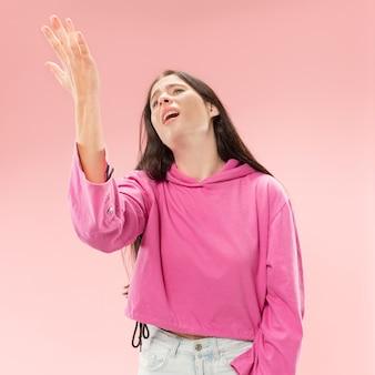 何故ですか。トレンディなピンクのスタジオの背景に分離された美しい女性のハーフレングスの肖像画。若い感情的な驚き、欲求不満、当惑した女性。人間の感情、顔の表情の概念。