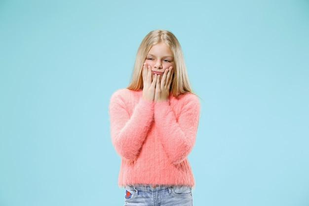 何故ですか。トレンディな青いスタジオの背景に美しい女性のハーフレングスの肖像画。若い感情的な驚き、欲求不満と当惑した十代の少女。人間の感情、表情の概念。