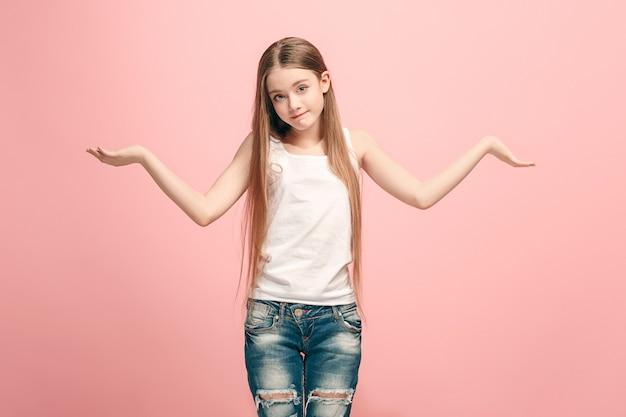 何故ですか。トレンディなピンクのスタジオの背景に美しい女性のハーフレングスの肖像画。若い感情的な驚き、欲求不満と当惑した十代の少女