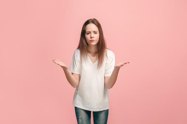 Это почему. красивый женский поясной портрет на модном розовом. молодая эмоциональная удивленная, разочарованная и сбитая с толку девушка-подросток