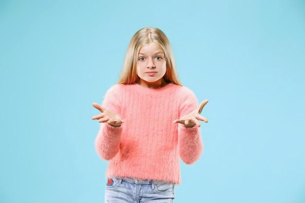 Perché. bello ritratto a mezzo busto femminile sul backgroud blu alla moda dello studio. giovane ragazza teenager sorpresa, frustrata e sconcertata emotiva. emozioni umane, concetto di espressione facciale.