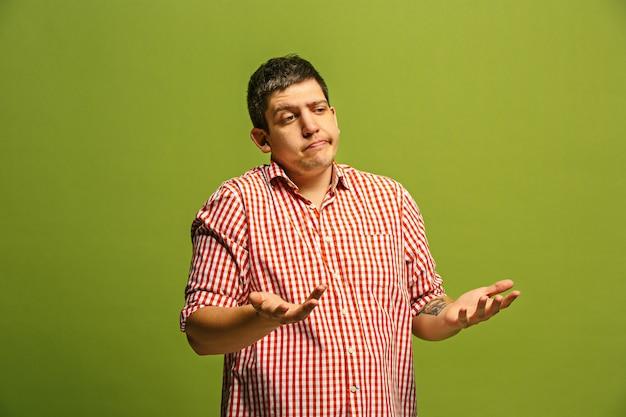 何故ですか。トレンディな緑のスタジオの背景に分離された美しい男性のハーフレングスの肖像画。若い感情的な驚き、欲求不満、当惑した男。人間の感情、表情の概念。