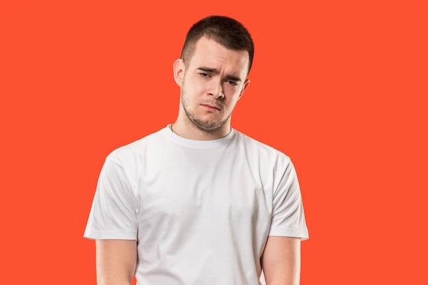 何故ですか。トレンディなオレンジ色のスタジオの背景に分離された美しい男性のハーフレングスの肖像画。若い感情的な驚き、欲求不満、当惑した男。