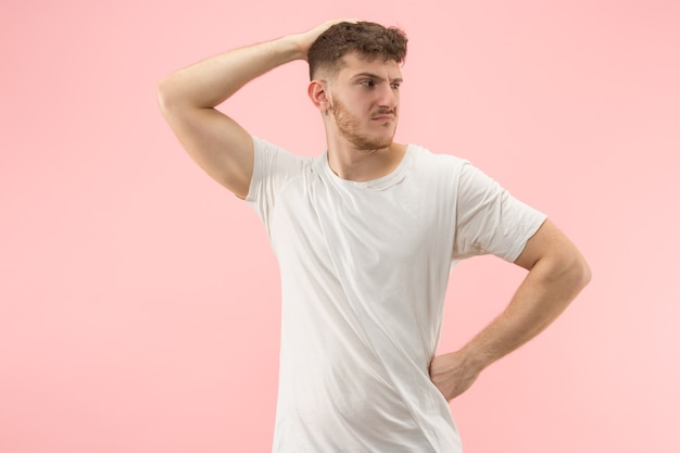 何故ですか。トレンディなピンクの背景に分離された美しい男性のハーフレングスの肖像画。若い感情的な驚き、欲求不満、当惑した男