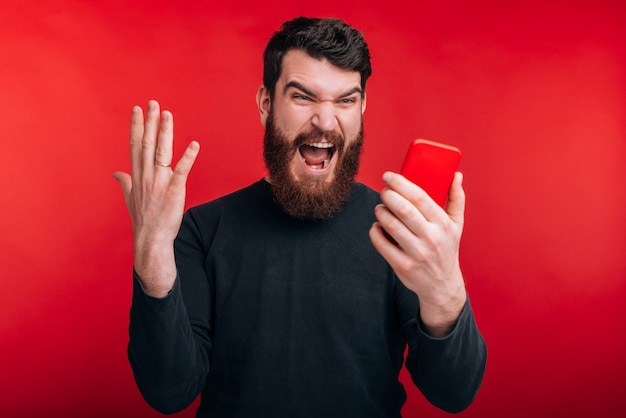 Why it doesn't work?! angry bearded man is shouting at this phone on red wall