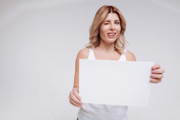 Почему ты такой серьезный. замечательная артистичная привлекательная женщина дурачится на съемочной площадке, корчит рожи и держа в руках белый знак