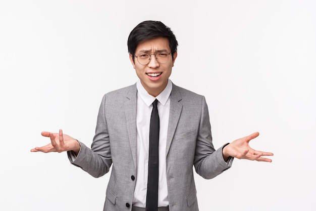 なぜあなたは何が欲しいのですか?グレーのスーツを着た悩みと欲求不満の若いアジア人男性のウエストアップ肖像
