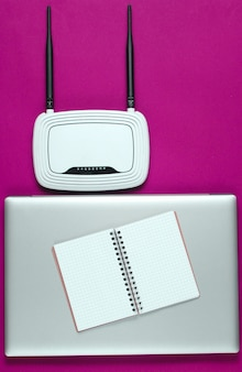 Wi fi router, laptop, pc mouse, notepad on pink background