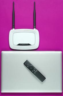 Маршрутизатор wi-fi, ноутбук, компьютерная мышь, пульт дистанционного управления на розовом фоне