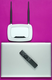 Wi fi router, laptop, pc mouse, remote controller on pink background