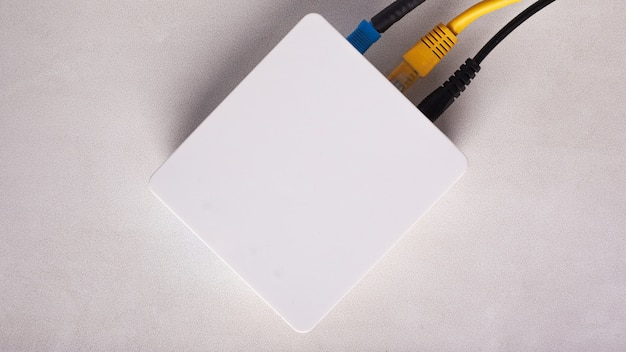 Wi-fi router modem with connected cables on a white background close-up top view.