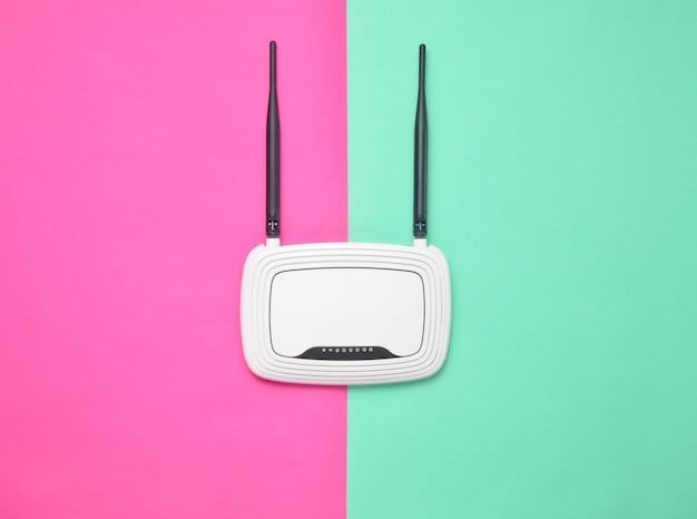 Маршрутизатор wi-fi на цветном пастельном фоне. тенденция минимализма. всегда онлайн. вид сверху.