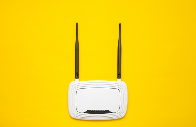 Маршрутизатор wi-fi на желтом фоне. тенденция минимализма. всегда онлайн. вид сверху.