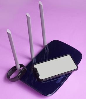 Wi-fiルーター、スマートフォン、紫色の背景のフィットネストラッカー