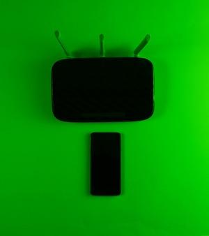 Wi-fiルーター、スマートフォン。現代のガジェット。グリーンネオンライト