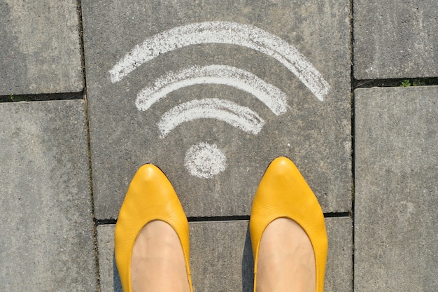 Wi-fi symbol on gray sidewalk with woman legs, top view