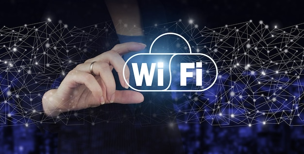 Wi fi wireless concept. hand hold digital hologram wi fi sign on city dark blurred background. free wifi network signal technology internet concept.