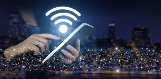 Wi fi wireless concept. hand touch white tablet with digital hologram wi fi sign on city dark blurred background. business networking connection concept and wi-fi in city.