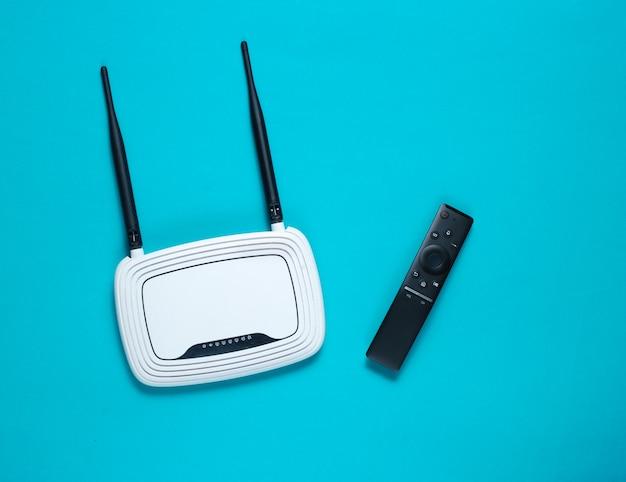 Wi fiルーター、青いテーブルにテレビのリモコン。上面図