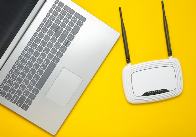 黄色の紙の背景にラップトップとwi-fiルーター。キーボード、タッチパッド。最新のデジタル技術。コピースペース。上面図。