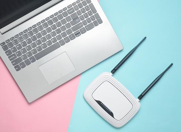Компьтер-книжка и маршрутизатор wi-fi на предпосылке цветной бумаги. клавиатура, тачпад. современные цифровые технологии. копировать пространство вид сверху.