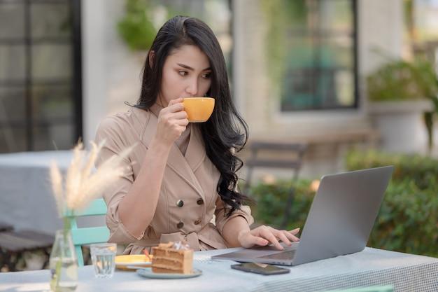 タイのデザイナービジネスマンwi-fiインターネット経由でラップトップ上で作業を押しながら座ってコーヒーとケーキを飲む