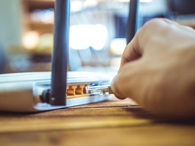 木製のテーブルのwi-fiルーターにイーサネットワイヤを挿入する手を閉じる