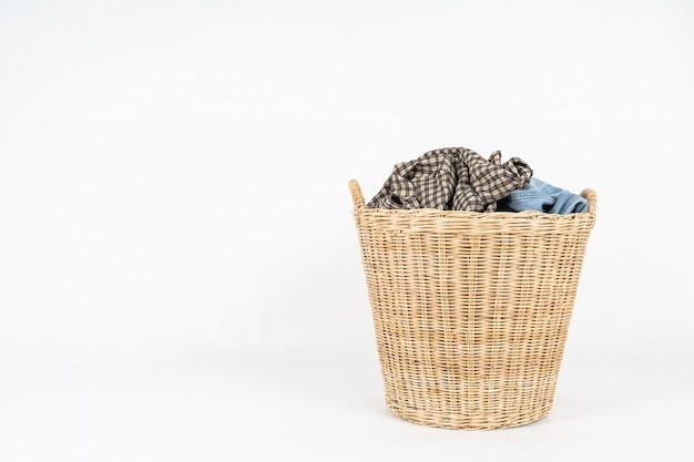 Wicker basket of clothes isolated on white