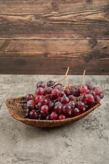 Wicker basket of delicious red grapes on marble table.
