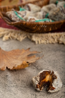 Wicker basket of dried sweet persimmons on stone table.