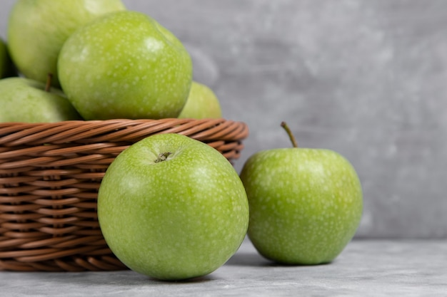 A wicker basket of fresh green apples on stone