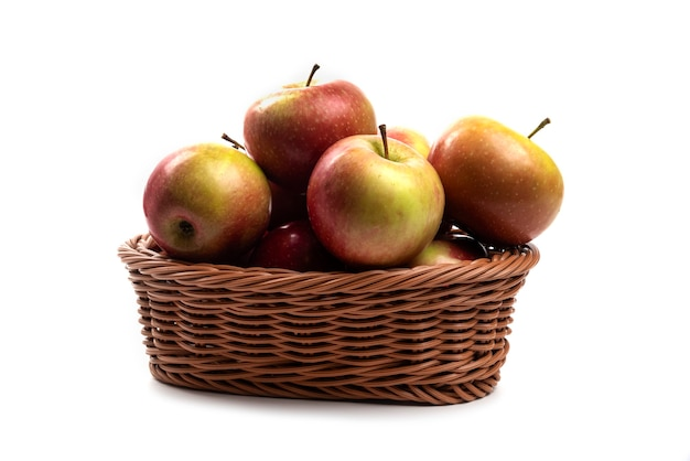 Wicker basket of fresh juicy apples isolated on white.