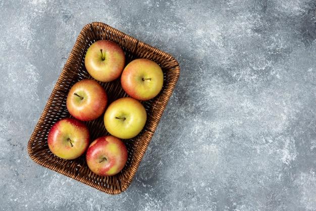 Cesto di vimini di mele fresche succose sulla superficie in marmo.