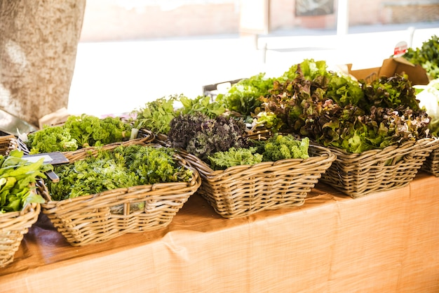 Wicker basket of fresh leafy vegetables arranged in row at market stall