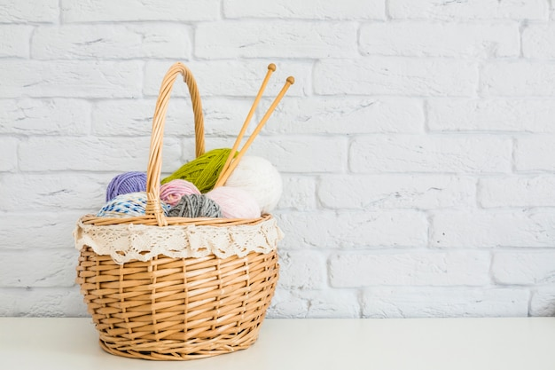Wicker basket full of colorful yarns in front of wall