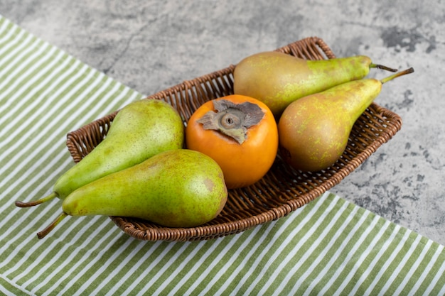 Wicker basket full of green pears and persimmon on stone.