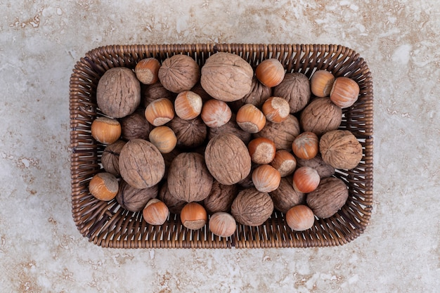 A wicker basket full of healthy macadamia nuts and walnuts placed on a stone surface.