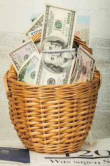 A wicker basket full of money over table