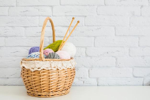 Плетеная корзина с красочными пряжами перед стеной