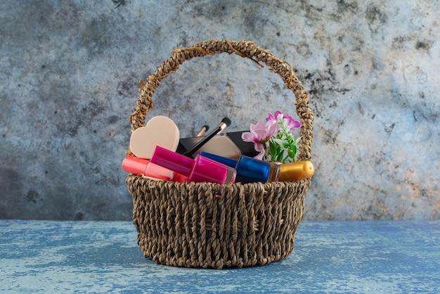 大理石の表面に装飾的な化粧品でいっぱいの籐のバスケット。