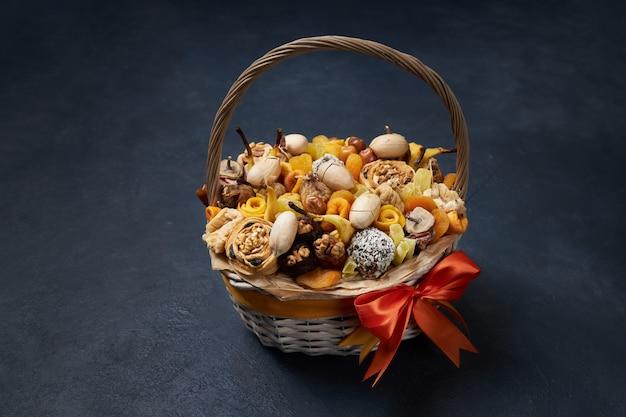 Плетеная корзина полна сухофруктов и экзотических орехов на синем фоне