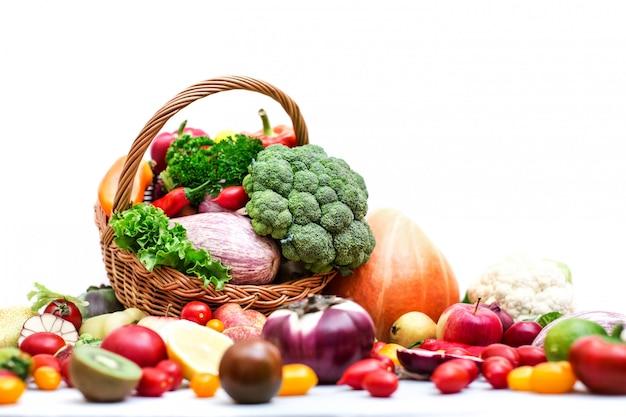 Плетеная корзина полна органических фруктов и овощей.